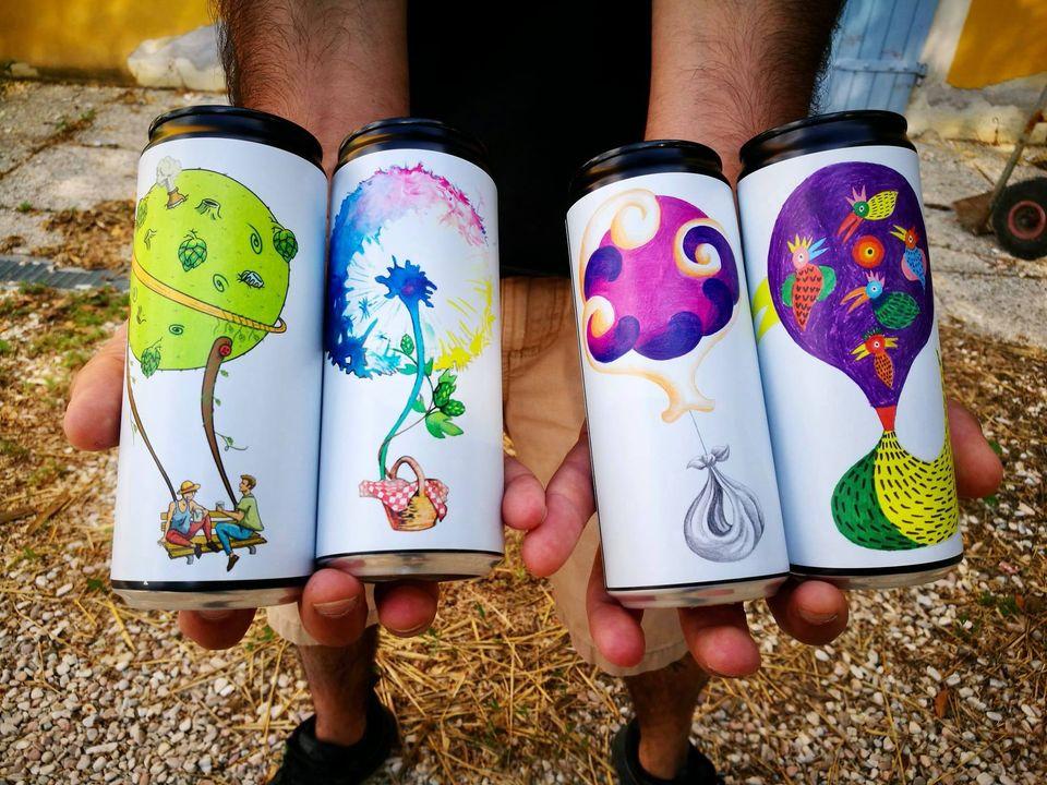 primo piano delle 4 nuove differenti lattine di birra colorate in mano ad un uomo