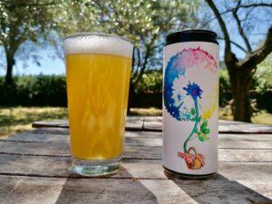 Una lattina di birra e una bicchiere di birra su un tavolo di legno nella natura